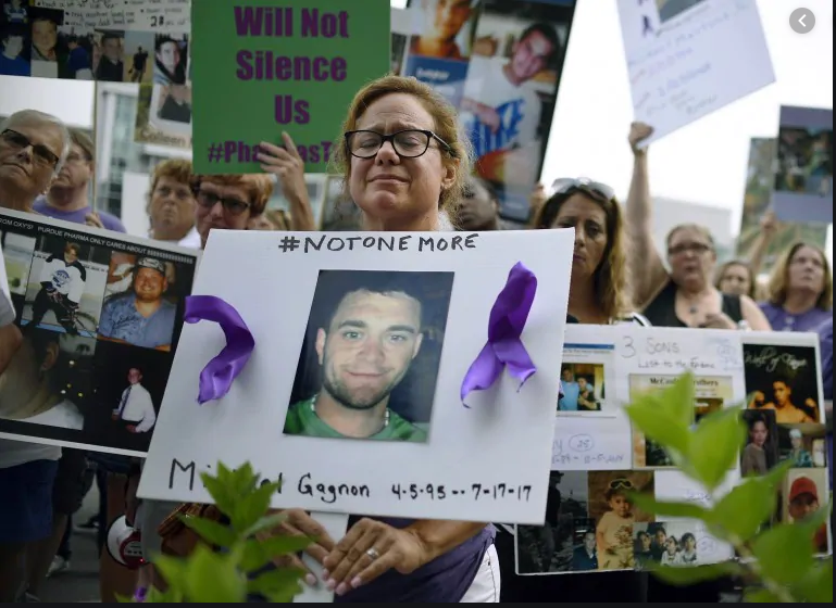 "A mourning woman at an Opioid Crisis rally holds a poster featuring a young man she lost to the crisis.   The poster uses the social media tag ""#NotOneMore""."